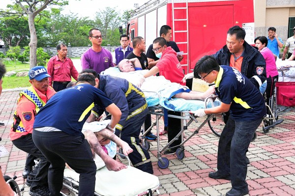 Paramedics attend to the injured on stretchers after a fire broke out at a nursing home in Pingtung County yesterday morning. Photo: Tsai Tsung-hsien, Taipei Times