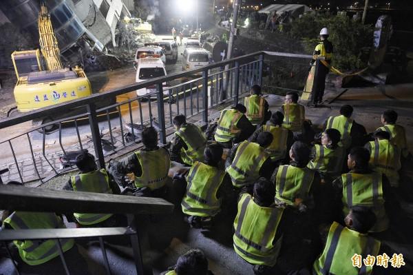 國軍協助搜救工作,搜救任務告一段落後,9日晚間在震災現場找一處席地而坐休息。(記者陳志曲攝)