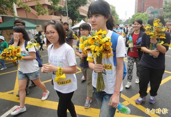 圖為太陽花學運,女學生送太陽花為堅守立院的學生加油打氣。(資料照)
