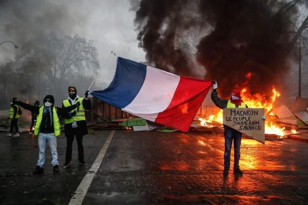 民眾高舉法國國旗,要求法國總統馬克宏下台。(法新社)