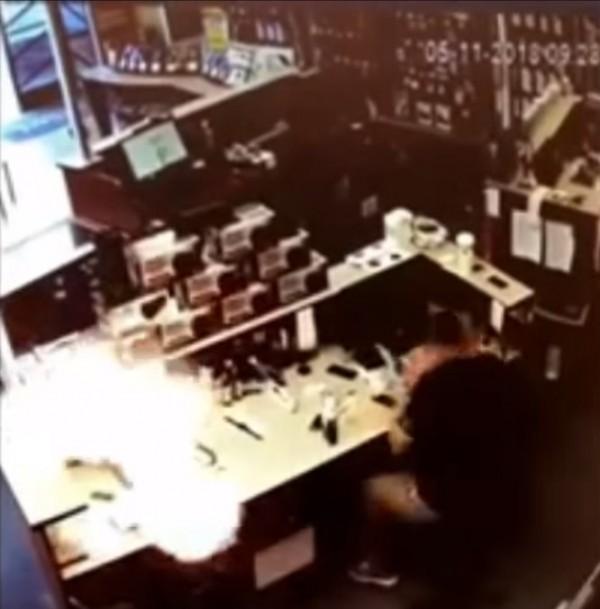 店員在一旁維修別支手機,沒想到桌面上的iPhone竟突然爆炸起火。(圖擷自《Youtube》)
