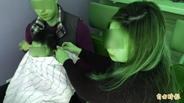 劉先生(左)抱著現已7個多月大的兒子,由太太(右)示範,他們從監視器畫面上看到,托嬰中心托育人員如何用包巾輕勒小嬰兒的脖子。(記者黃美珠攝)