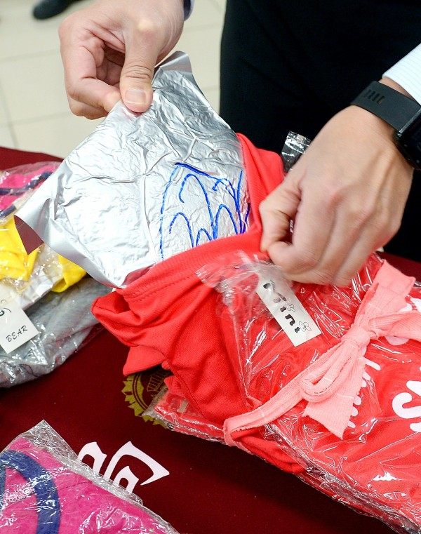 A worker at the Investigation Bureau's Taipei branch yesterday displays a package of MDMA allegedly smuggled into the nation in a shipment of clothing. Photo: Lin Cheng-kung, Taipei Times