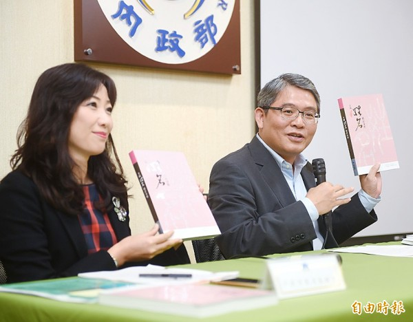 Department of Household Registration Affairs Director Wanda Chang, left, holds up a book as Deputy Minister of the Interior Hua Ching-chun speaks at a news conference in Taipei yesterday for the release of a survey on the nation's surnames. Photo: Chu Pei-hsiung, Taipei Times