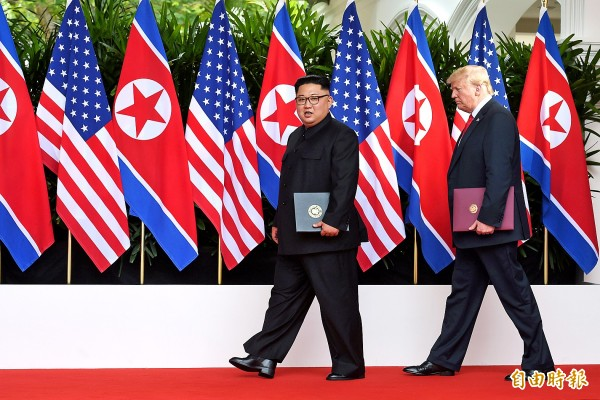 North Korean leader Kim Jong-un, left, and US President Donald Trump walk during their summit at the Capella Hotel on Sentosa island, Singapore, yesterday.