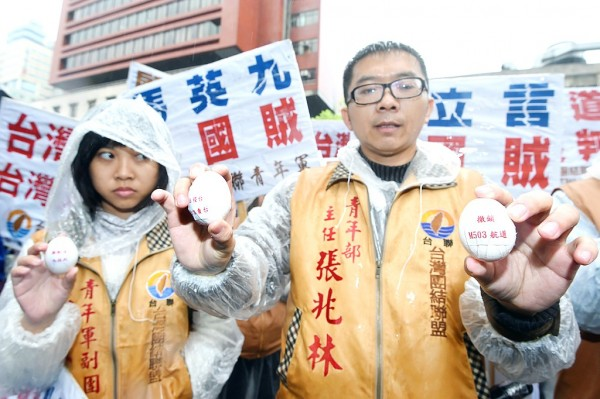 Members of the Taiwan Solidarity Union yesterday show eggs they brought to throw at the Mainland Affairs Council building in Taipei, as they protest against China's opening of the M503 flight route. Photo: Fang Pin-chao, Taipei Times