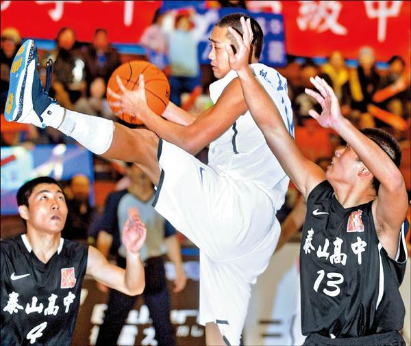 南湖高中鄧玉辰(中)躍起搶下籃板球,泰山高中兩名球員在旁防守;鄧玉辰昨全場攻得22分,率隊以81:65搶下8強賽首勝。(記者廖振輝攝)