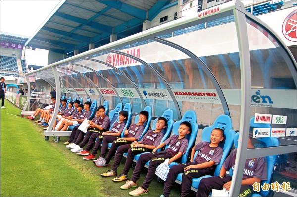 來自新北新市和台南文化國小的小球員,受邀參觀日本職業足球隊球場,坐在球員休息區編織未來的職業足球夢。(記者黃照敦攝)