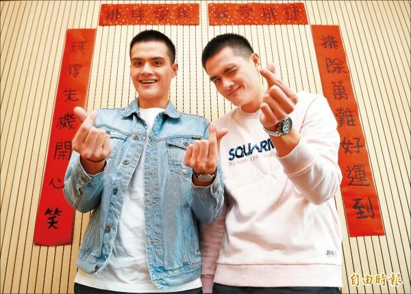 排球「電眼雙胞胎」劉鴻敏(右)與劉鴻杰(左)以愛心指祝賀新年快樂。(記者陳志曲攝)