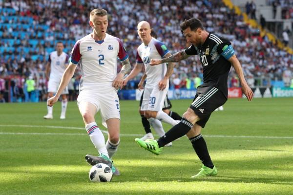 冰島先發右後衛沙瓦森(左)限制梅西(中)的發揮,助冰島成功逼和阿根廷。(路透)