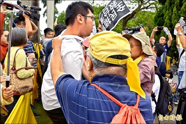 頭戴黃帽、藍上衣的老伯抓著潘姓同學(白衣者)的後衣領,最後致其受傷。(記者吳柏軒攝)