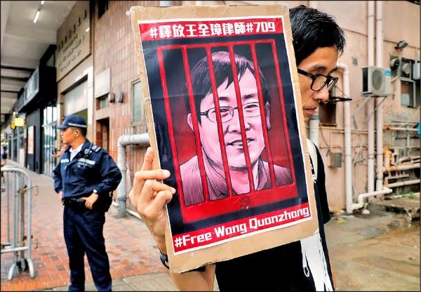 一名抗議者在劉曉波逝世周年紀念活動上, 拿著被監禁的中國人權律師王全璋照片,要求中國釋放。(美聯社檔案照)