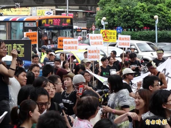 約有數百民眾在風雨中參與遊行。(記者蘇芳禾攝)