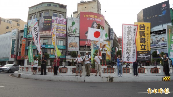 公投護台灣聯盟嘉義旗隊在嘉市地標中央噴水圓環舉旗歡迎田邊憲司,田邊也拿著日本國旗加入舉旗行列,吸引路過民眾目光。 (記者丁偉杰攝)