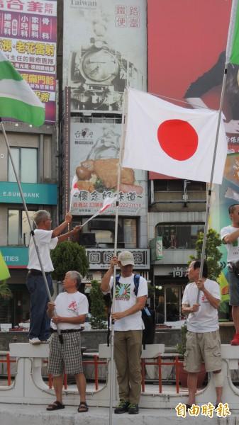 公投護台灣聯盟嘉義旗隊在嘉市地標中央噴水圓環舉旗歡迎田邊憲司,田邊也拿著日本國旗加入舉旗行列。 (記者丁偉杰攝)