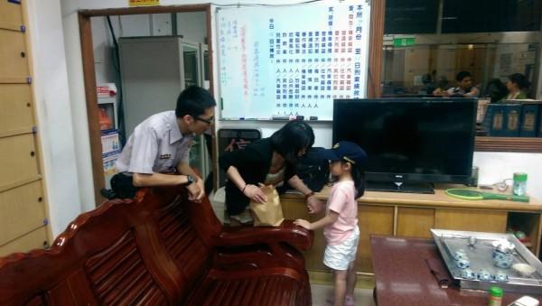 員警蔡明儒把自己的帽子送給小妹妹,中間為小妹妹的母親。(記者徐聖倫翻攝)