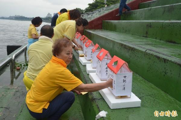 中元普度放水燈,廟方人員在水燈內放上金紙等物品燃燒。(記者葉永騫攝)