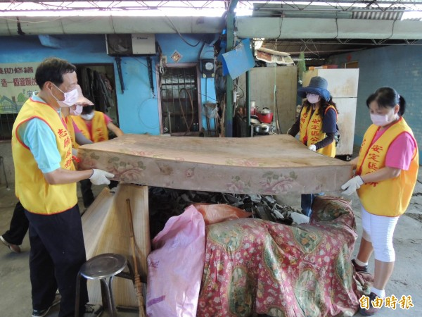 志工們清除不堪使用的家具、物品。(記者林孟婷攝)
