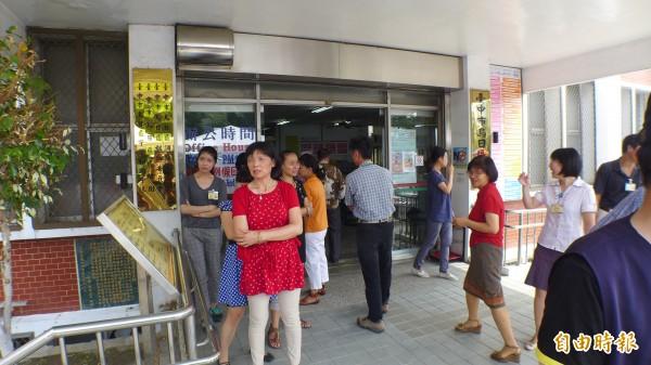 烏日區公所門口有多位職員等待「摸彩報號」,深怕錯過中獎機會。(記者俞泊霖攝)