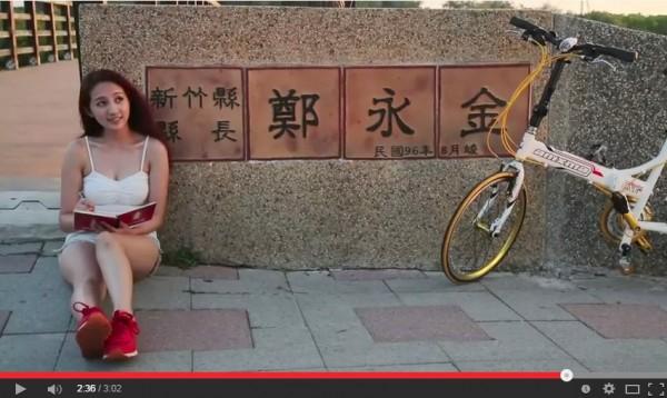 新竹縣長參選人鄭永金的清新篇電視廣告用單車正妹當主角。(畫面擷取自影片)
