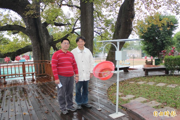 新竹縣文山國小校長王恭志(右)、教導主任郭榮治(左)身旁的就是保護身後3棵老楓香樹的「太陽能誘蟲器」。(記者黃美珠攝)