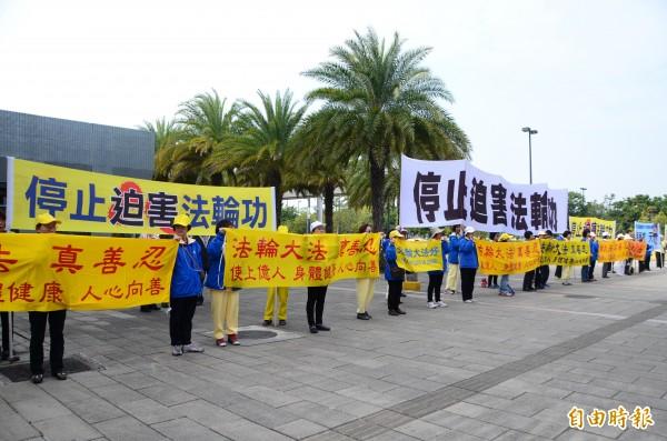 法輪功成員在台南高鐵站外舉出布條,抗議陳德銘。(記者吳俊鋒攝)