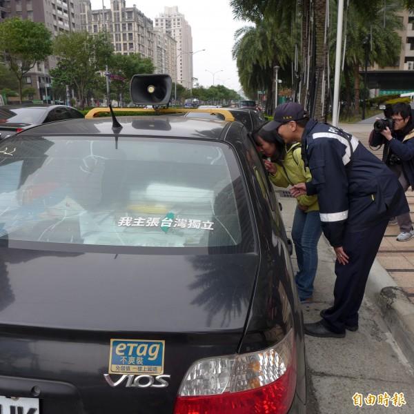 一名男子將貼有「我主張台灣獨立」貼紙的轎車停在飯店門口,用大聲公播放「島嶼天光」歌曲,最後在員警勸說下離開。(記者王駿杰攝)