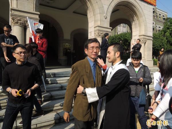 祁家威(著咖啡色上衣者)與律師團成員擁抱,感謝協助聲請釋憲。(記者項程鎮攝)