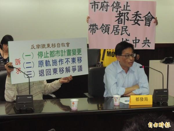 自救會在都發局官員發言時,舉牌重申他們的訴求。(記者蔡文居攝)