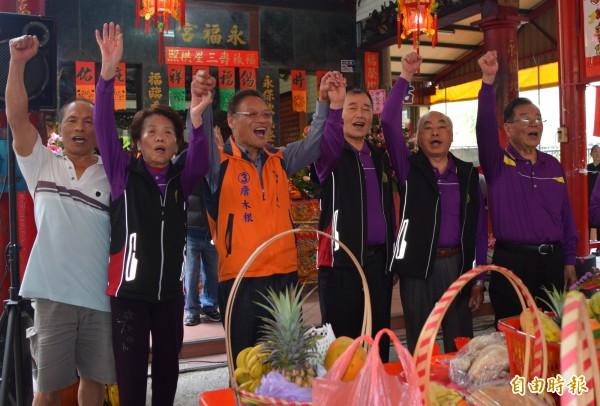 無黨籍永靖鄉長候選人詹木根(左3)在永福宮與支持者高呼「凍蒜!」(記者湯世名攝)