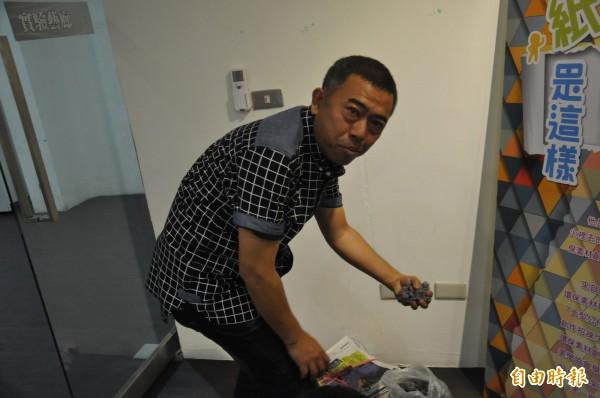 當廚師的劉勇良,手上抓著一把,不是食材,而是報紙團,是創作素材。(記者黃明堂攝)