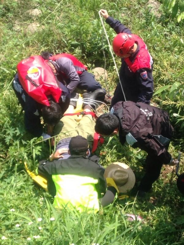 柑園消防分隊隊員從草叢中救出暈倒的老翁。(圖片民眾提供)