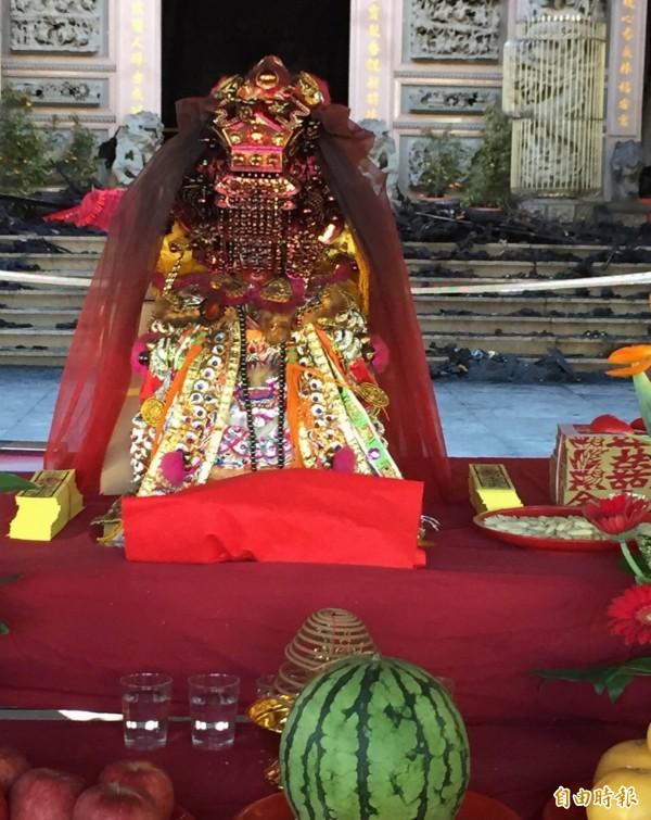 福安宮300多年歷史的「開基媽」神尊今天凌晨尋獲,已被大火燒成黑炭,廟方以紅布包覆,放在爐主媽祖前讓信徒膜拜。(記者湯世名攝)