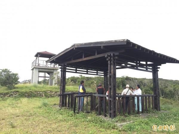 日治時代屏東縣高士村的高士神社現在只剩下4根木柱和屋頂,佐藤(左邊穿白衣者)屢次訪台在舊神社和當地相關人士商討神社復元工作。(圖︰佐藤健一提供)