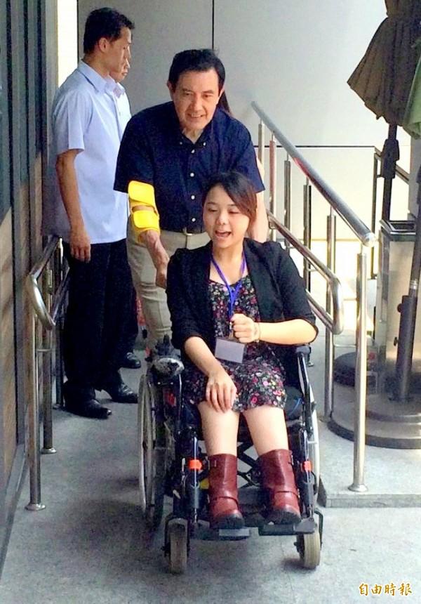 總統馬英九今上午體驗身障生活,協助輪椅族上下斜坡。(記者郭逸攝)