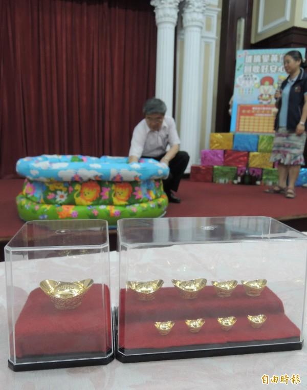環保局推出玻璃變黃金活動,鼓勵廢玻璃瓶回收,局長洪正中抽出金元寶得獎者。(記者蔡淑媛攝)