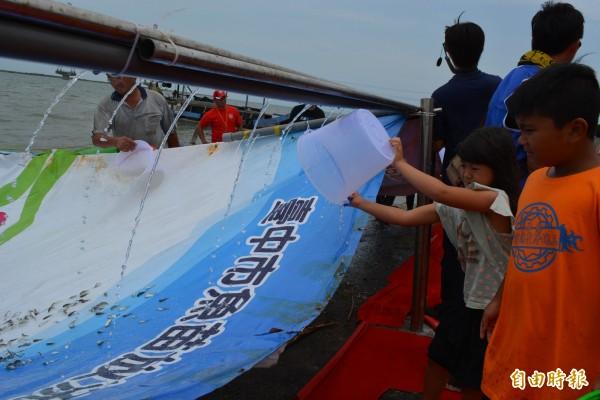 市府農業局今天結合宗教團體,在麗水漁港舉辦魚苗放流活動,吸引小朋友到場參加。(記者陳建志攝)