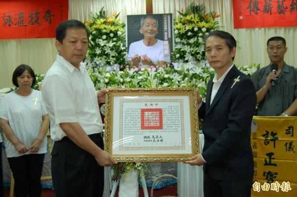文化部文資局副局長張仁吉(前右)代表總統馬英九頒發褒揚令給枝德師,由其長子廖志峯(前左)接受。(記者楊金城攝)