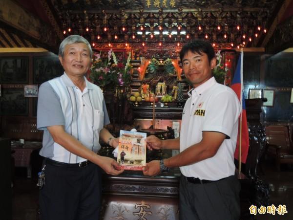 總教練仁志敏久(右)與飛虎將軍同鄉,主委吳進池(左)贈送日文簡介。對飛虎將軍受台灣人建廟奉祀,他十分感動。(記者蔡文居攝)