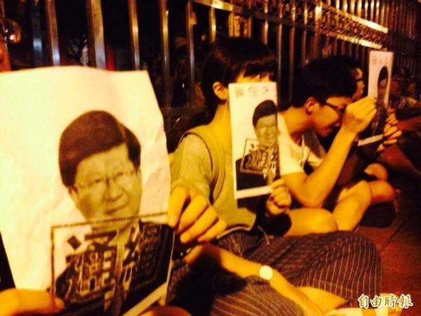 學生手持吳思華照片在立院大門口靜坐。(記者邱燕玲攝)