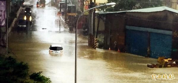 湳仔溪水暴漲,淹沒環河道路,小客車車身泡水動彈不得。(記者陳韋宗攝)