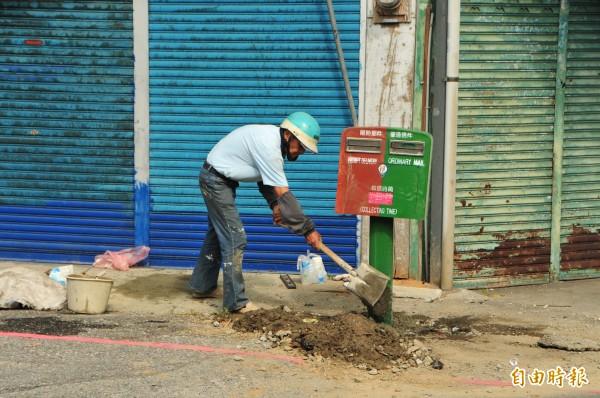 郵局週二突然雇請工人,將玉里歪腰郵筒挖開地基、整根「扶正」。(記者花孟璟攝)