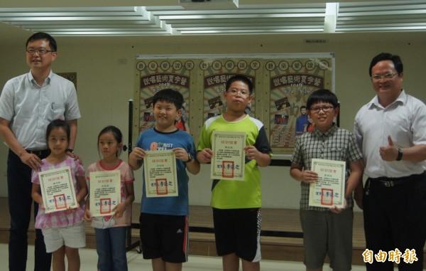 台南市議員李退之(左一)和新營新進國小校長黃耿鐘(右一)頒獎給參加說唱藝術夏令營的小朋友。(記者楊金城攝)