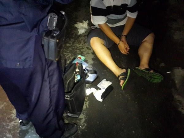 張姓男子(右)被警方壓制在地後,自黑色袋中搜出槍械、毒品。(記者黃良傑翻攝)