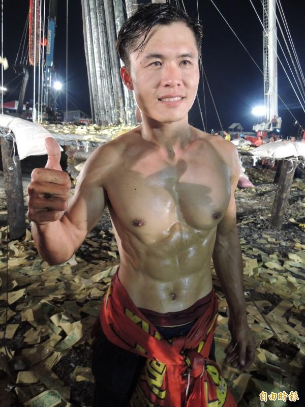 率先爬上孤頂的林宗麟,秀出肌肉線條,被封為「搶孤猛男」。(記者江志雄攝)