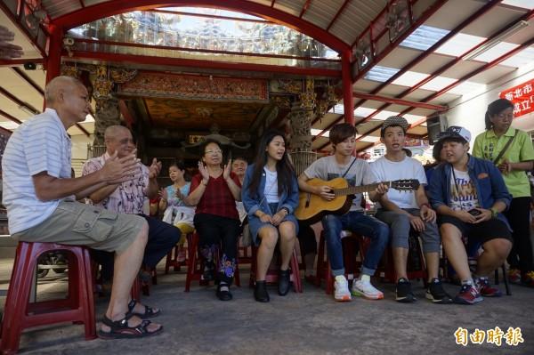 「阿貓阿狗公車男」樂團在祖田里信仰中心慈安宮廟埕前演唱《祖田之歌》,里民們也跟著打拍子合唱,直呼好聽、感人。(記者張安蕎攝)