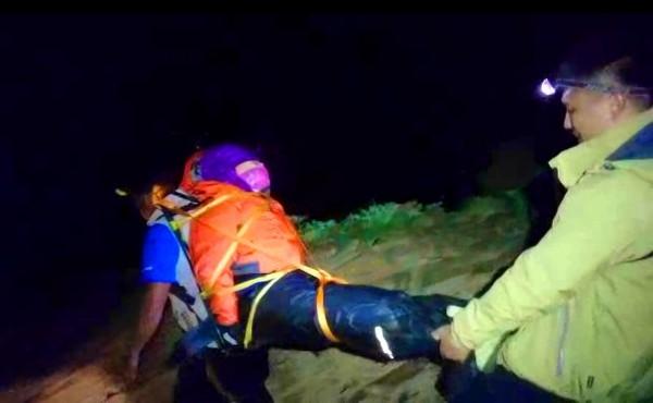 女登山客被搜救人員一揹一抬,送下山救治。(記者陳鳳麗翻攝)