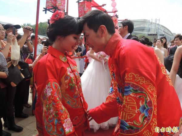 「我們結婚了!」51隊佳偶今天參加新竹縣集團結婚,在竹北體育館外花海景觀區,北管八音團演奏中,循客家禮俗完成終生大事。(記者廖雪茹攝)