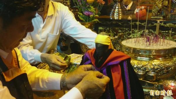 穀豐宮人員為神農大帝穿上博士袍。(記者余雪蘭攝)