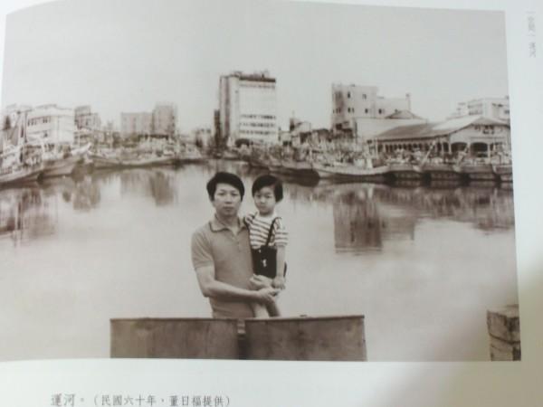 畫家董日福抱兒子合影於運河盲段對岸,遠處高樓即是合作大樓,右邊是台南漁市場。(翻攝自台南市文化基金會出版《圖像府城》)